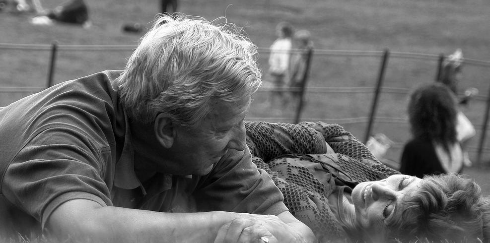 pareja senior tumbada parque