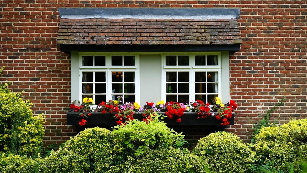 ventana jardinera flores fachada piedra