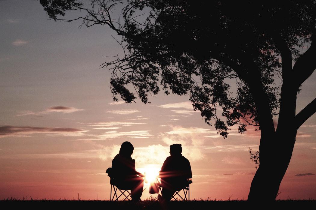 personas sentadas puesta de sol